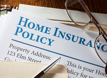 Home Insurance Policy form in a file folder with a pair of glasses resting on top